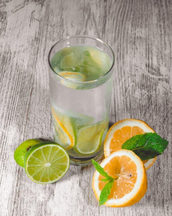 Kalk en citroenplons met ijs en wat detoxwater royalty-vrije stock foto