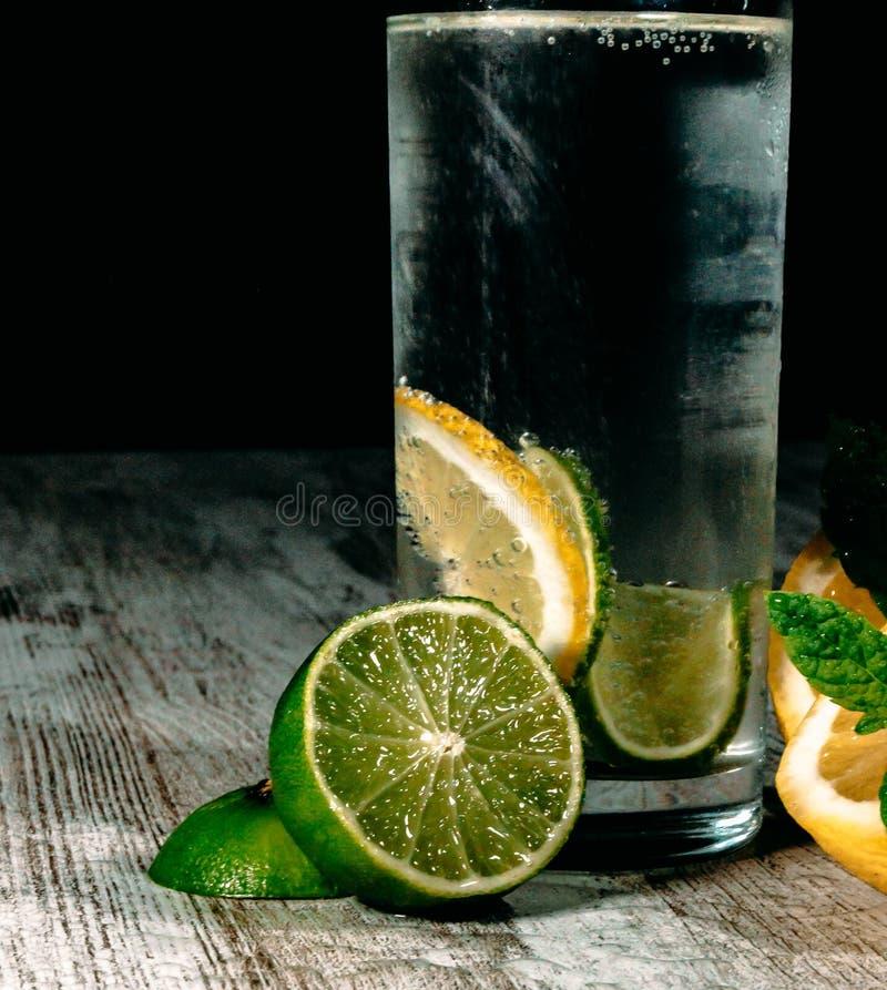 Kalk en citroenplons met ijs en wat detoxwater royalty-vrije stock foto's