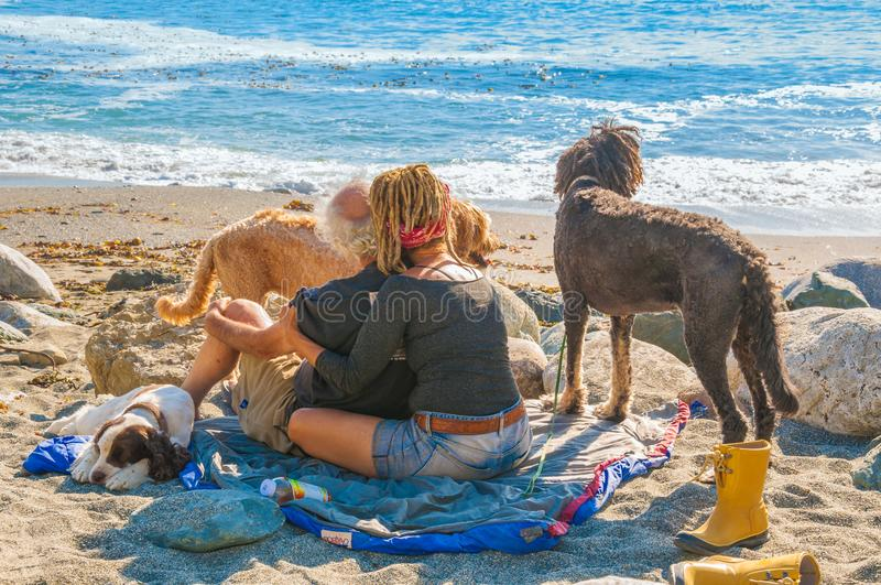 KALKOFEN-NATIONALPARK, KALIFORNIEN - 10. September 2015 - Mitte alterte Hippiepaare mit drei Hunden am Strand stockbild