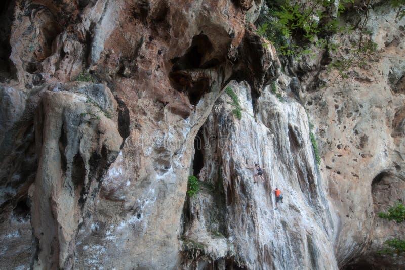 Kalksteenmuur met toerist het beklimmen in Krabi-provincie stock afbeeldingen