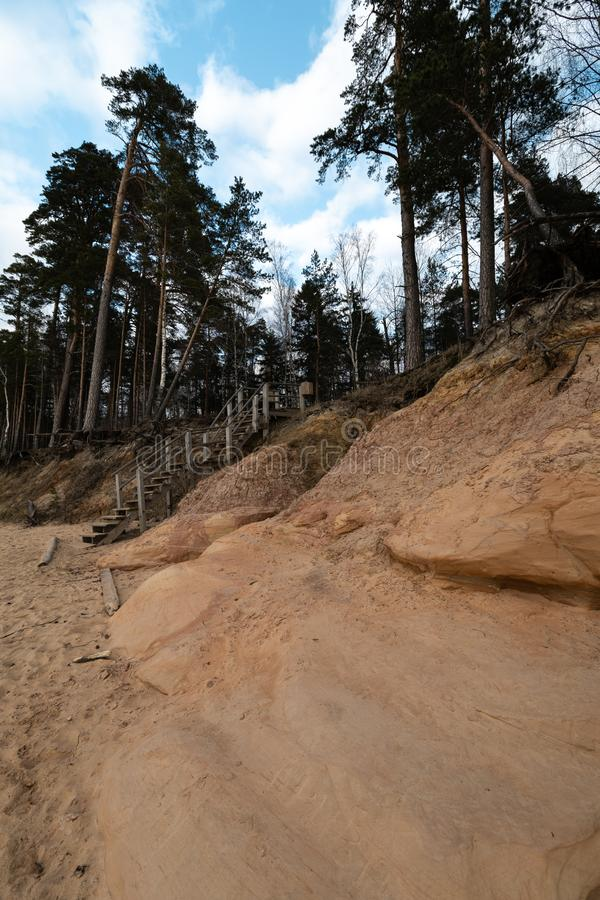 Kalksteenstrand bij de Oostzee met mooi zandpatroon en levendige rode en oranje kleur - Toeristengeschrift op royalty-vrije stock foto