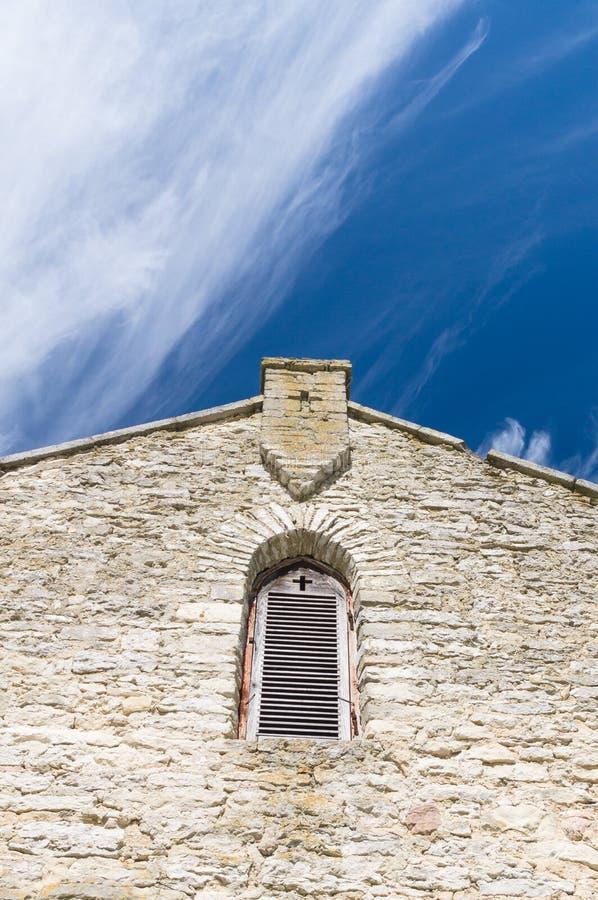 Kalksteinfassade der alten Kirche mit Fensterfensterladen und -kreuz stockbild
