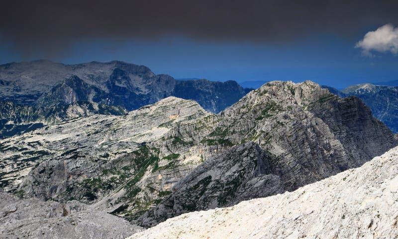 KalkstenVeliko Spicje maximum under mörka moln, Julian Alps royaltyfria bilder