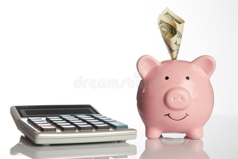 Kalkulator i ceramiczny różowy prosiątko bank z dolarowym pieniądze obraz stock