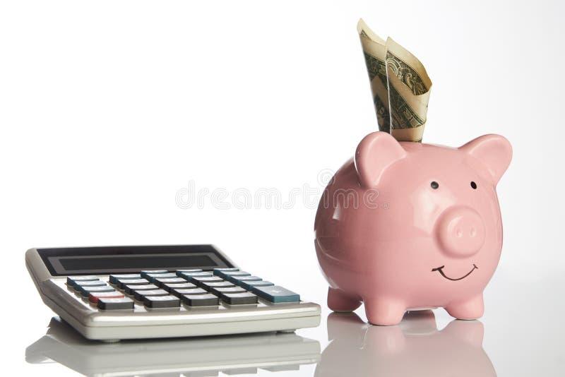 Kalkulator i ceramiczny różowy prosiątko bank z dolarowym pieniądze zdjęcie stock