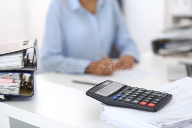 Kalkulator i segregatory z papierami czekamy przetwarzającym biznesowej kobiety lub księgowej plecy w plamie wewnętrzny obraz royalty free