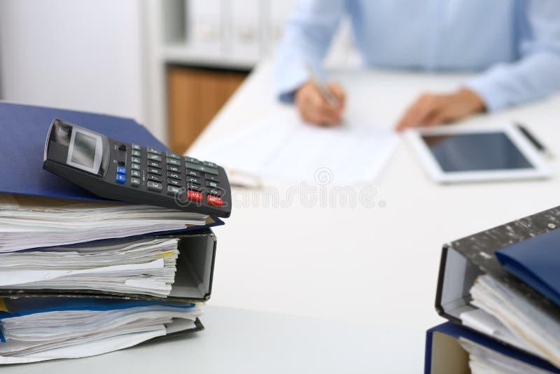 Kalkulator i segregatory z papierami czekamy przetwarzającym biznesowej kobiety lub księgowej plecy w plamie wewnętrzny obrazy stock