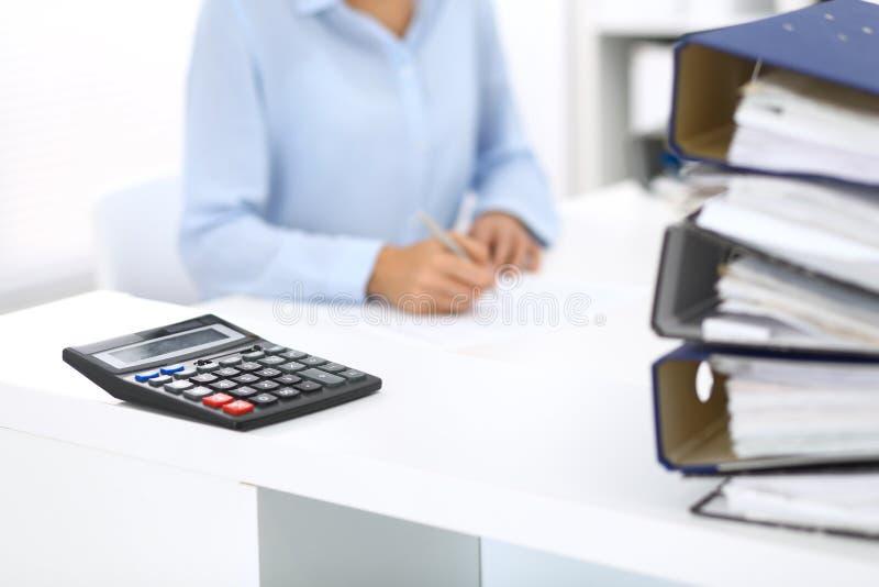 Kalkulator i segregatory z papierami czekamy przetwarzającym biznesowej kobiety lub księgowej plecy w plamie wewnętrzny fotografia royalty free