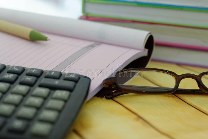 Kalkulator, oczu szkła, pióro, kwit i fakturowa książka, i brogujący książki w tle fotografia stock
