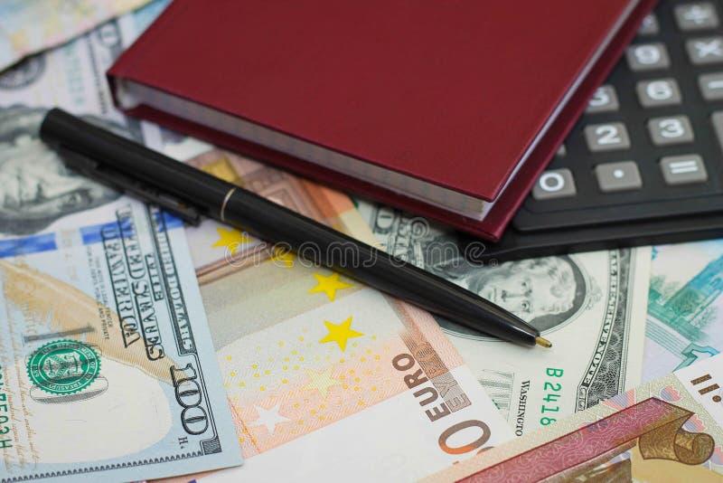 Kalkulator, pióro i Notepad na tle pieniądze, obraz royalty free
