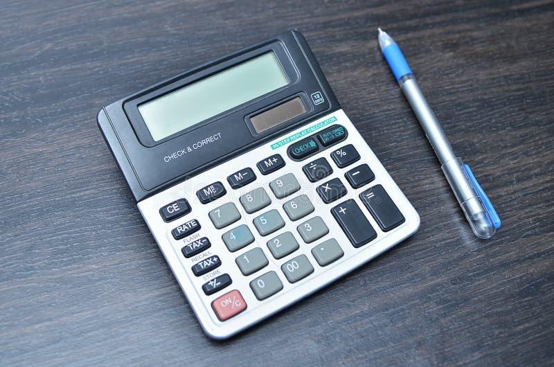 Kalkulator z piórem na drewno deski tle obraz stock