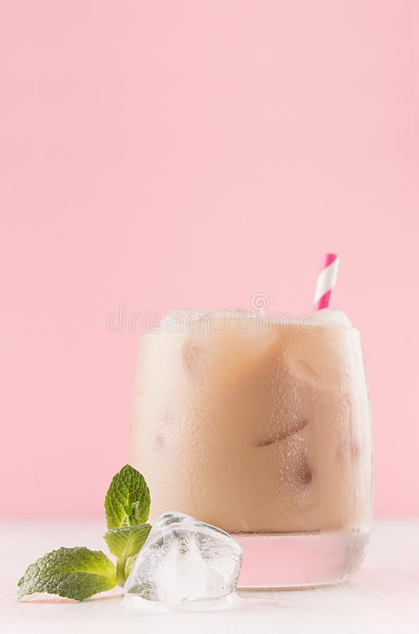 Kall alkoholcoctail för kaffe i bägare med iskuben, grön mintkaramell, randigt sugrör i pastellfärgat ljus - rosa modern restaura royaltyfria foton
