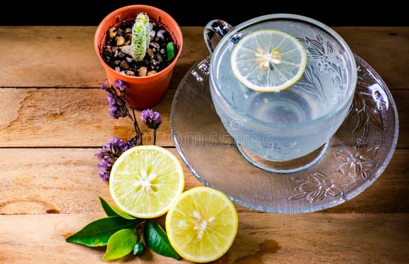 Kall citronsodavatten, läsk tjänade som i härlig crystal kopp med den lilla maträtten på trätabellen, den nya örtdrinken för häls arkivfoto