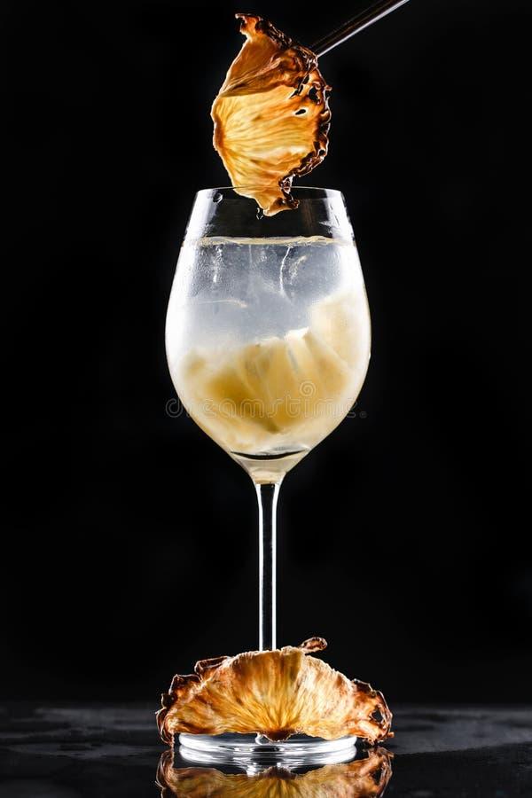 Kall coctail med ananas och is i högväxt exponeringsglas på svart bakgrund Sommardrinkar och alkoholiserade coctailar royaltyfri bild