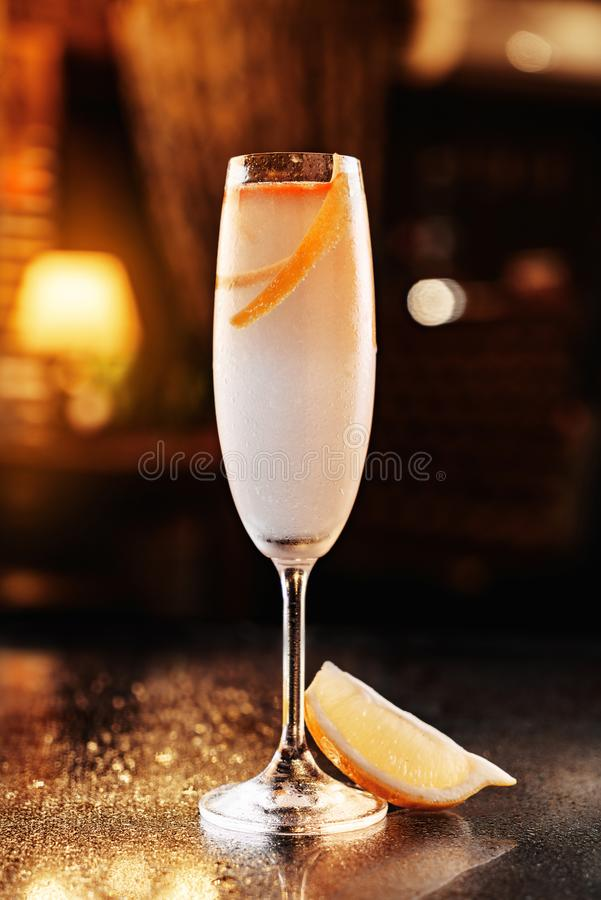 Kall coctail med citronen och champagne i högväxt exponeringsglas på bakgrunden av restaurangatmosfären Sommardrinkar och coctail royaltyfria bilder