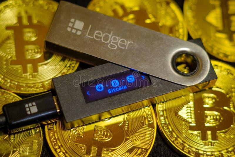 Kall crypto plånbokhuvudbok Nano S som ligger på guld- bitcoinmynt arkivfoton