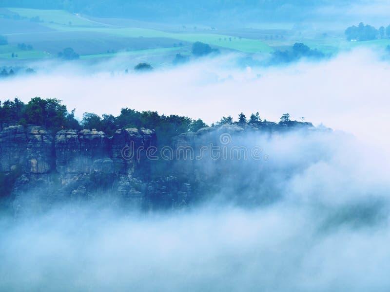 Kall dimmig blå morgon En minut för soluppgång i en härlig dal av stenigt parkerar Trädmaxima royaltyfria bilder
