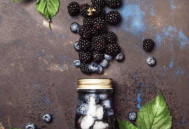 Kall drink för sommarbärfrukt med blåbär, björnbär och is i glasflaskan, brun köksbordbakgrund, kopieringsutrymme, royaltyfri bild