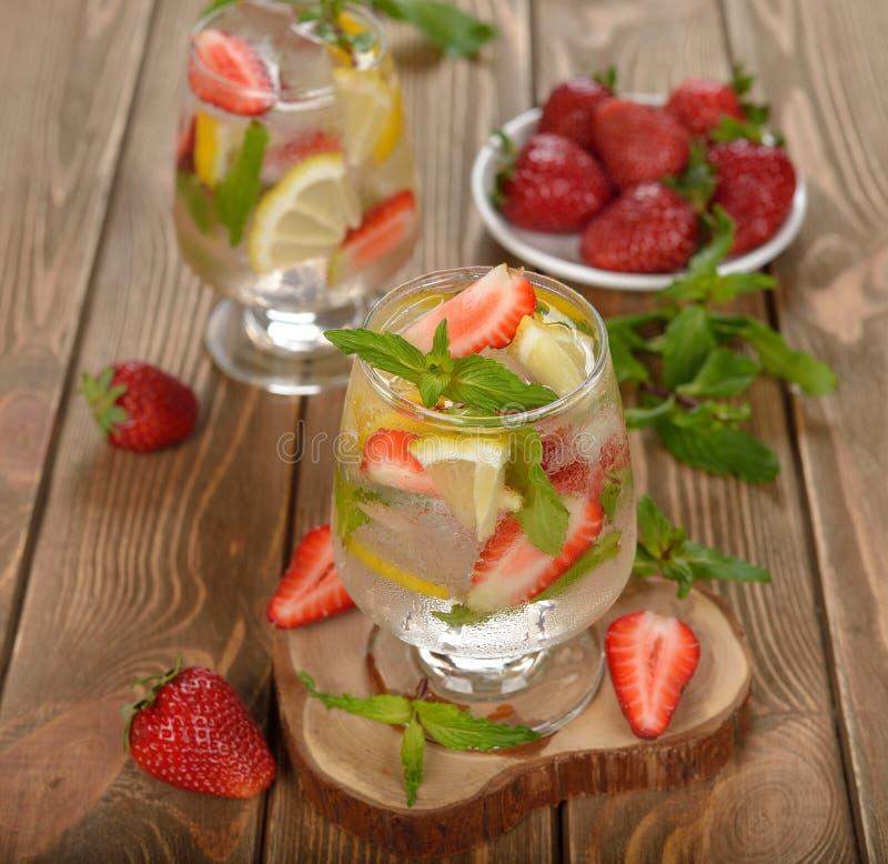 Kall drink med jordgubbar, citronen och mintkaramellen arkivbild