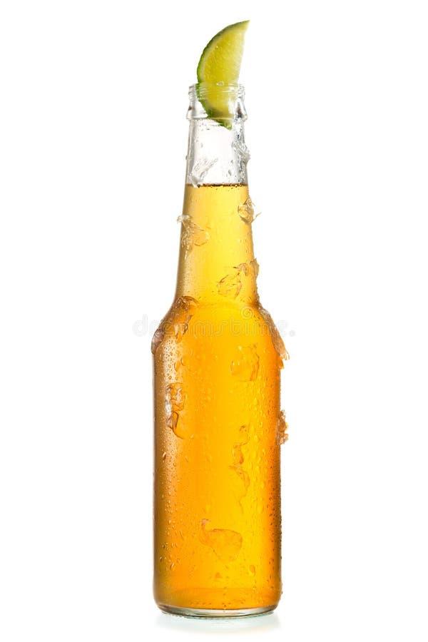 Kall flaska av öl med limefrukt arkivbild