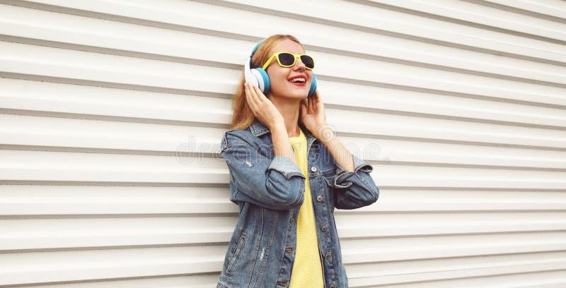 Kall flicka i trådlös hörlurar som tycker om att lyssna till musik på stadsgatan över den vita väggen fotografering för bildbyråer