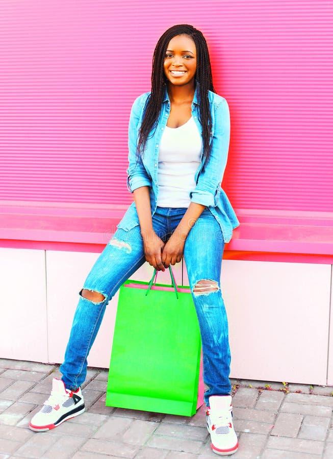 Kall flicka med shoppingpåsar i stad över färgrika rosa färger arkivbild