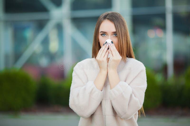 kall influensa Den unga attraktiva flickan, fångade en förkylning på gatan, torkar hennes näsa med en servett fotografering för bildbyråer