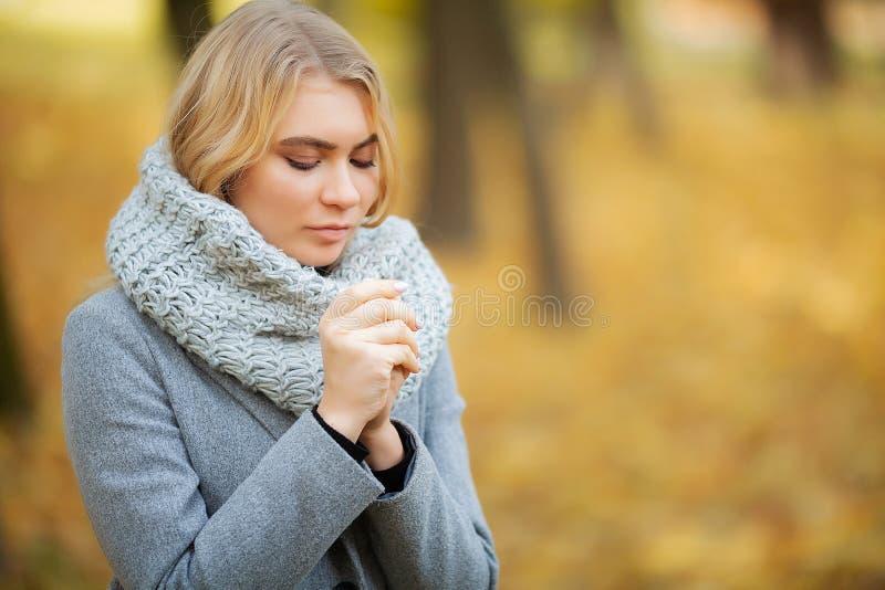 kall influensa Den unga kvinnan i ett grått lag som går i hösten, parkerar och värme den djupfrysta handen fotografering för bildbyråer