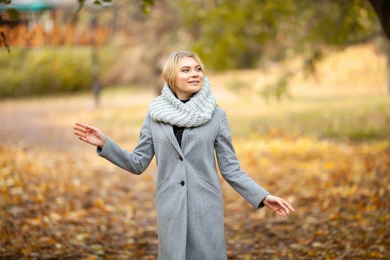 kall influensa Den unga kvinnan i ett gr?tt lag som g?r i h?sten, parkerar och v?rme den djupfrysta handen arkivbild