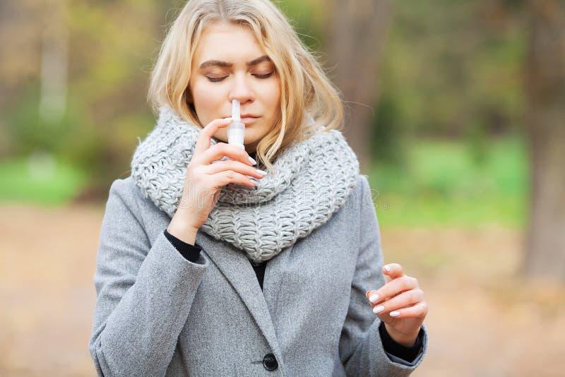 kall influensa Den unga sjuka kvinnan använder en nässprej på gatan utanför royaltyfria bilder