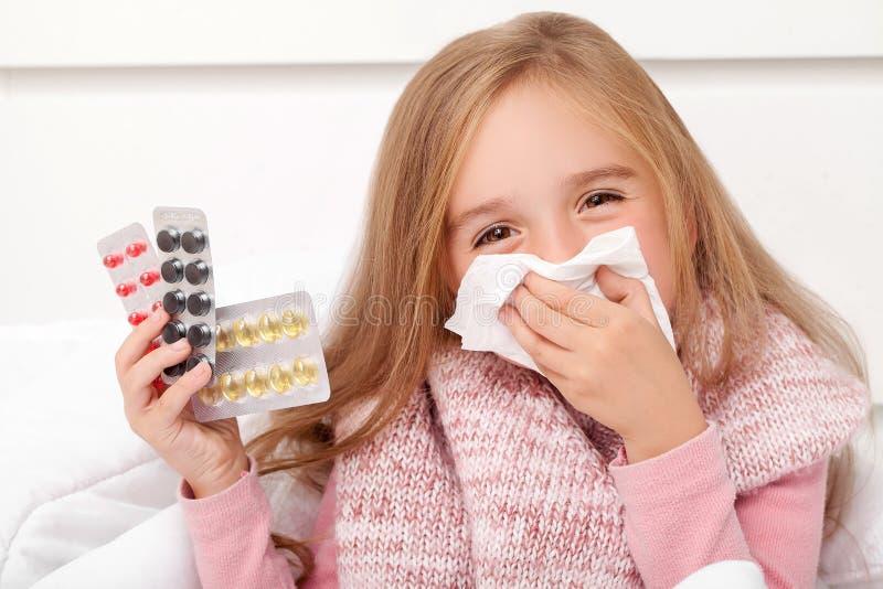 kall influensa En flicka med preventivpillerar i hennes händer arkivbild