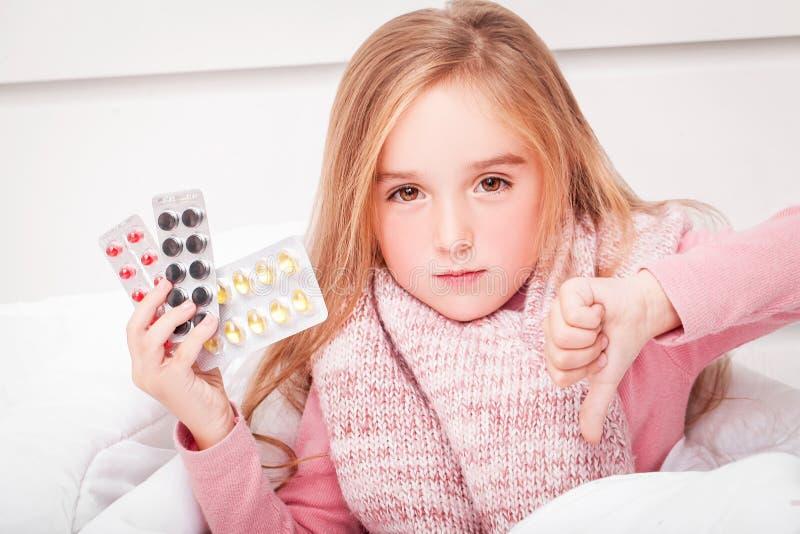 kall influensa En flicka med preventivpillerar i hennes händer arkivbilder