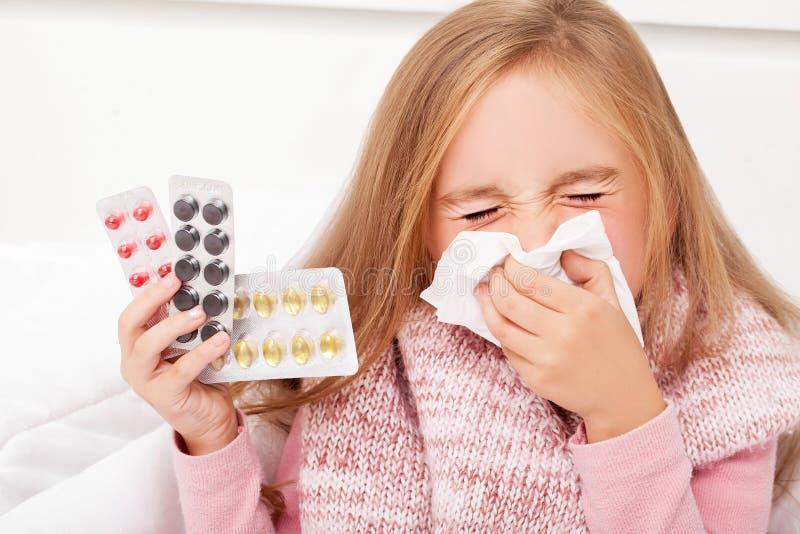 kall influensa En flicka med preventivpillerar i hennes händer royaltyfri fotografi