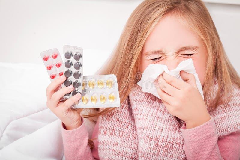 kall influensa En flicka med preventivpillerar i hennes händer royaltyfria bilder