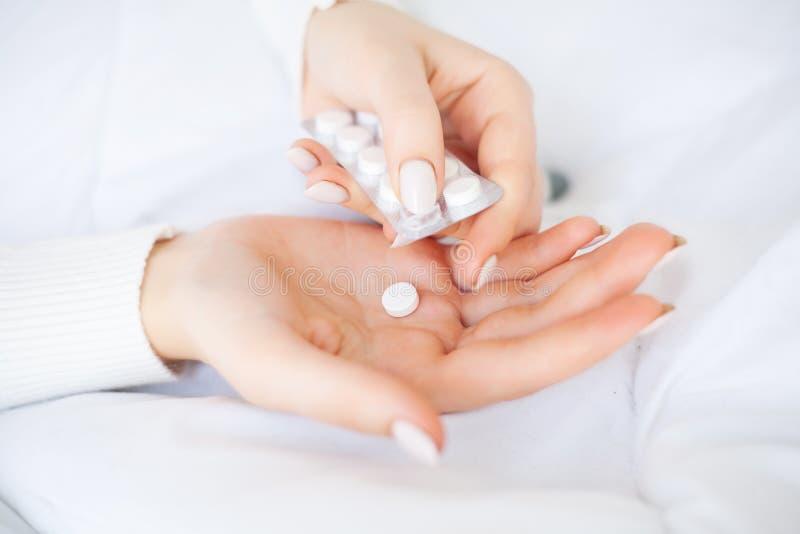 kall influensa Kvinnahållpiller i handen som ligger på sängen arkivfoton