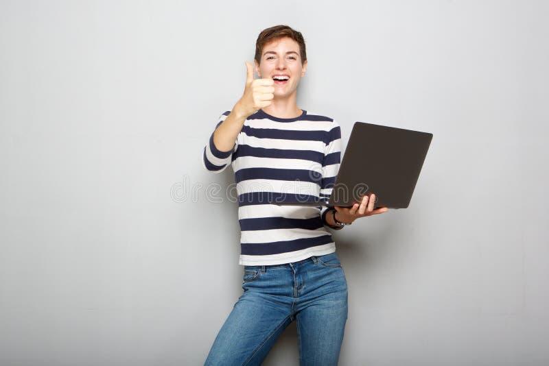 Kall innehavbärbar dator för ung kvinna och med tummar upp handtecken arkivfoton