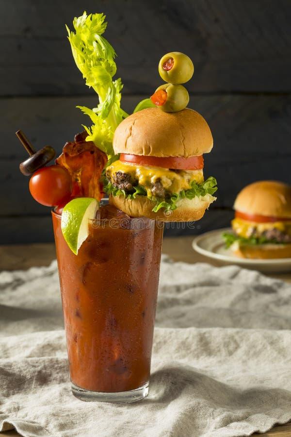 Kall iskall gourmet- Bloody Mary med en hamburgare royaltyfri fotografi