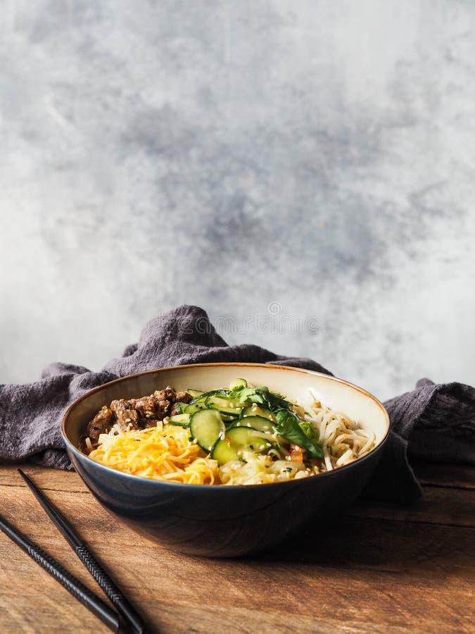 Kall koreansk kuksisoppa med grönsaker, förvanskade ägg, nötkött och nudlar i en bunke och pinnar på lantlig träbakgrund royaltyfri bild