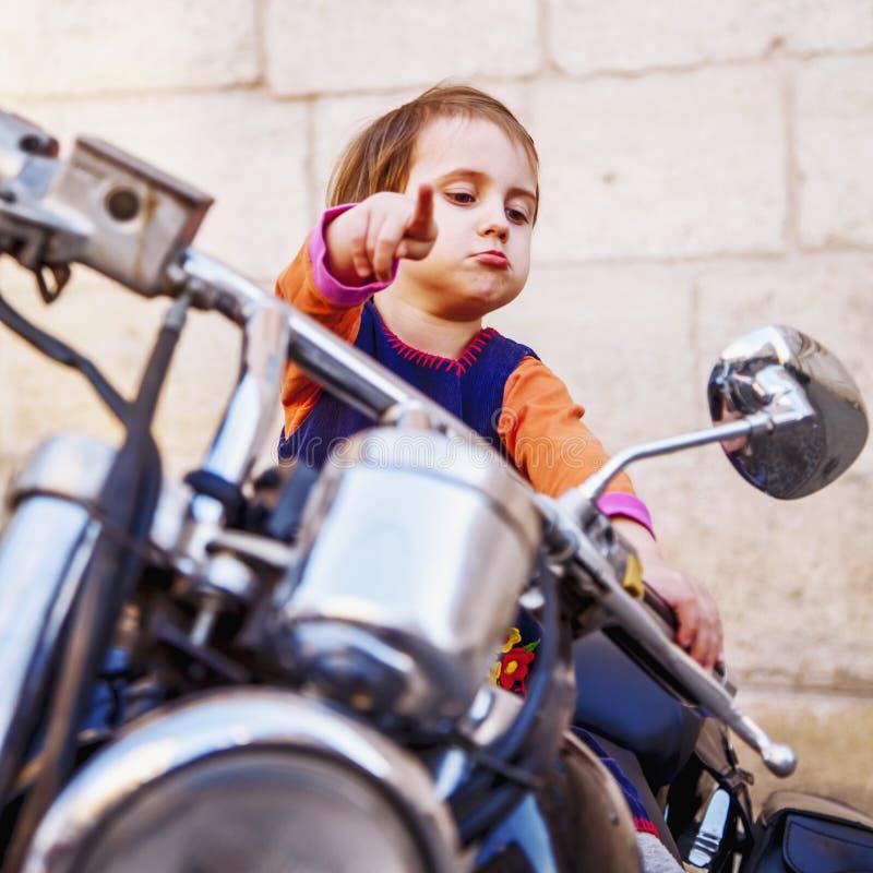 Kall liten cyklistflicka som spelar och har gyckel p? den danade motorcykeln Humoristisk st?ende av barnpunkter till v?gen med fi royaltyfri fotografi