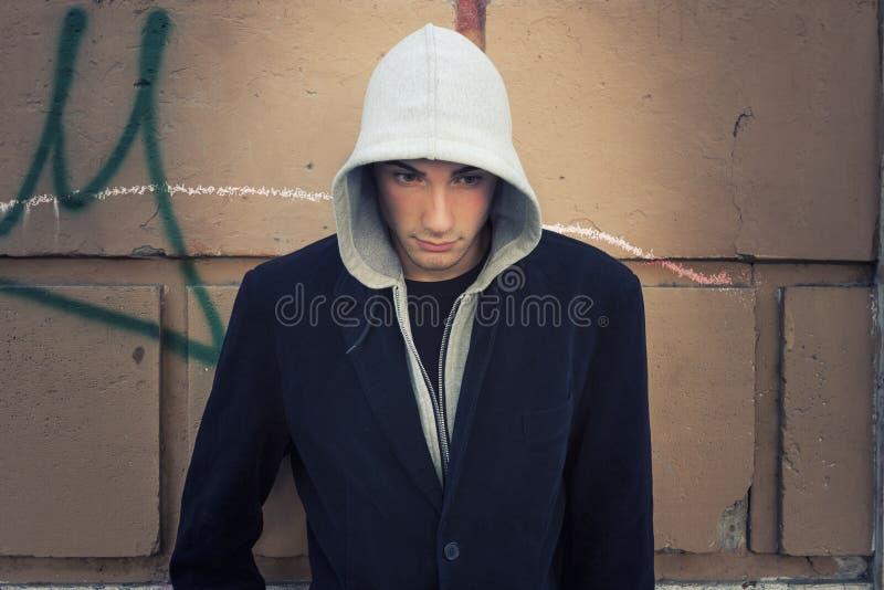 Kall manmodell med hoodien, väggbakgrund royaltyfri foto