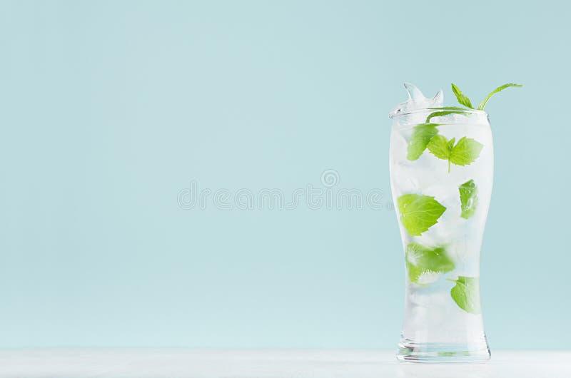 Kall mintkaramelldrink för ny sommar med det gröna bladet, iskuber, uppiggningsmedel i ljus mjuk pastellfärgad blå färgbakgrund p arkivfoton