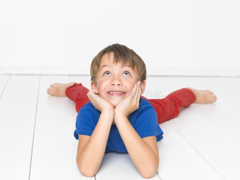 Kall och gullig och härlig sex årig pojke med röd byxa och den blåa skjortan på det vita golvet arkivbild