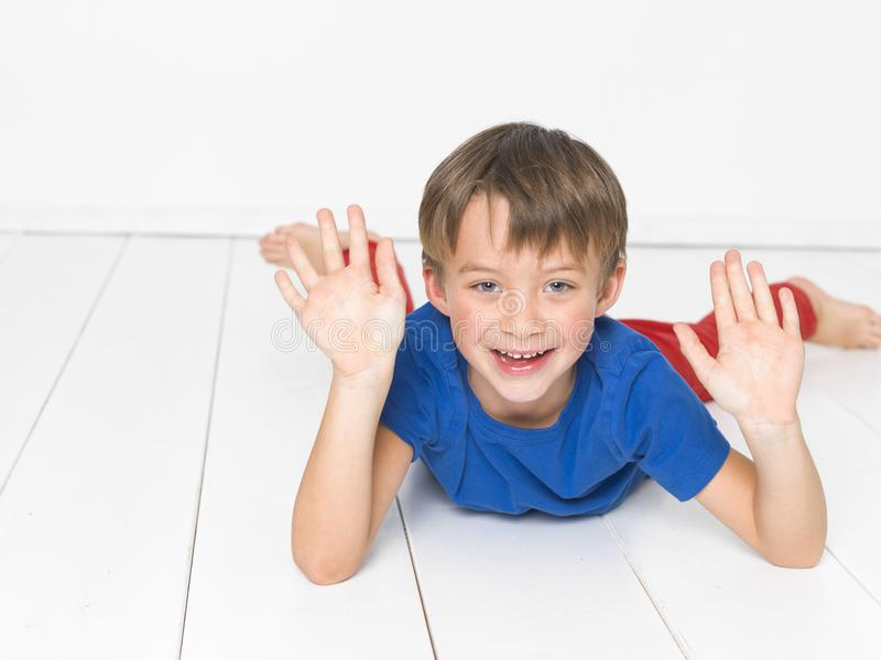 Kall och gullig och härlig sex årig pojke med röd byxa och den blåa skjortan på det vita golvet fotografering för bildbyråer