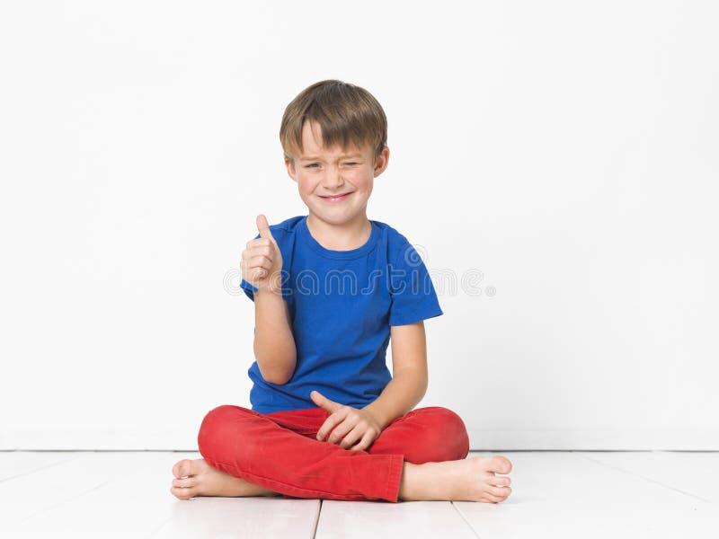 Kall och gullig och härlig sex årig pojke med röd byxa och den blåa skjortan på det vita golvet royaltyfria foton
