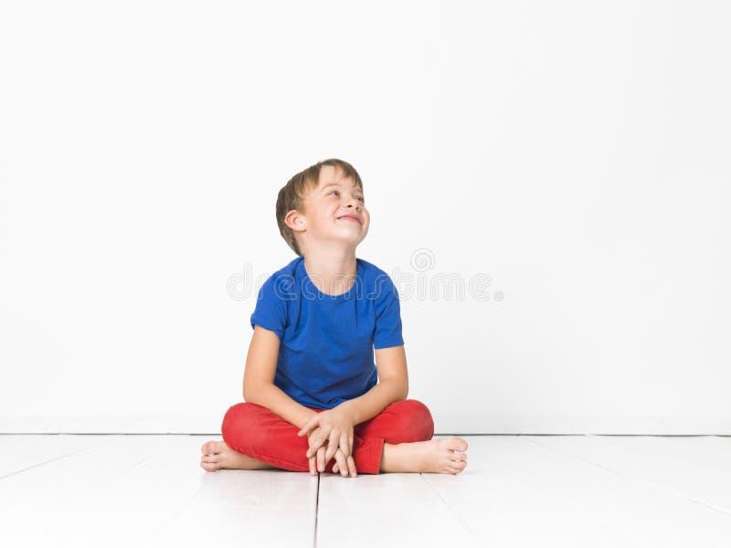 Kall och gullig och härlig sex årig pojke med röd byxa och den blåa skjortan på det vita golvet royaltyfria bilder