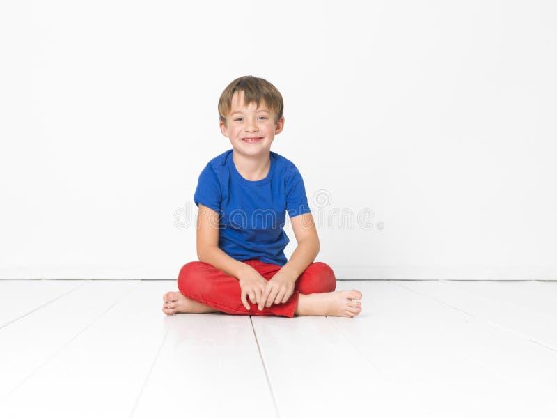 Kall och gullig och härlig sex årig pojke med röd byxa och den blåa skjortan på det vita golvet arkivfoton