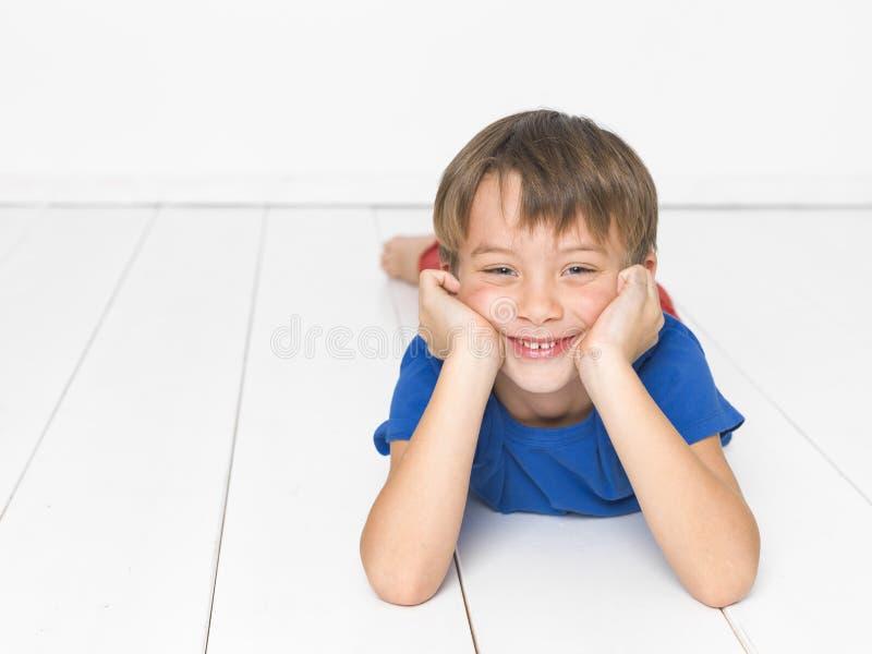 Kall och gullig och härlig sex årig pojke med röd byxa och den blåa skjortan på det vita golvet royaltyfri fotografi