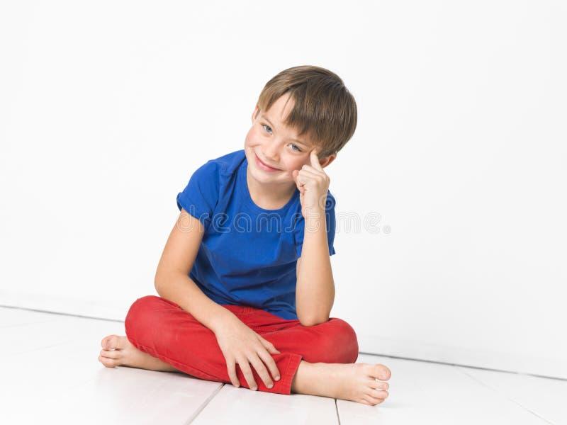 Kall och gullig och härlig sex årig pojke med röd byxa och den blåa skjortan på det vita golvet royaltyfri foto