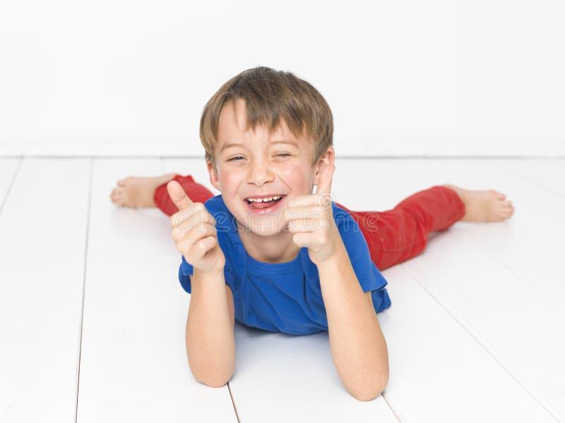 Kall och gullig och härlig sex årig pojke med röd byxa och den blåa skjortan på det vita golvet arkivfoto