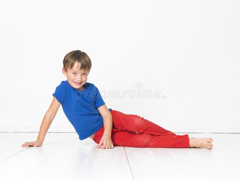 Kall och gullig och härlig sex årig pojke med röd byxa och den blåa skjortan på det vita golvet arkivbilder